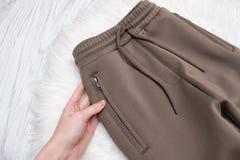 Bruine broeken met ritssluitingen in vrouwelijke hand modieus concept Stock Afbeeldingen
