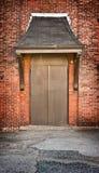 Bruine deur bij de baksteenbouw Stock Afbeelding