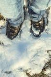 Bruine die laarzen in sneeuw worden behandeld Stock Fotografie
