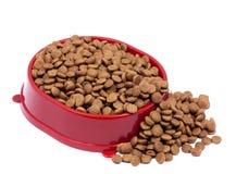 Bruine droge kat of hondevoer in rode die kom op witte achtergrond wordt geïsoleerd Stock Afbeeldingen