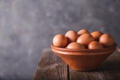 Bruine eieren in een bruine ceramische kom op houten lijst aangaande een grijze samenvatting bbackground Rustieke stijl Eieren Pa Stock Foto's