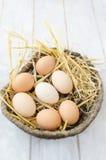 Bruine eieren in een rieten mand Royalty-vrije Stock Foto's