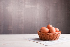 Bruine eieren in een rieten mand aan een lichte houten lijst en een kant Royalty-vrije Stock Fotografie