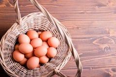 Bruine eieren in een rieten mand met een handvat op een bruine lijstbovenkant Stock Afbeelding