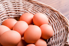 Bruine eieren in een rieten mand op een bruine mening van de lijstbovenkant Royalty-vrije Stock Afbeeldingen