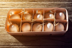 Bruine eieren in houten kom op houten achtergrond Stock Foto
