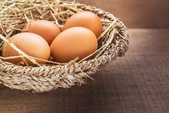 Bruine eieren in mand op houten lijst Stock Afbeeldingen