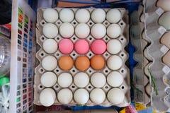 Bruine eieren witte eieren en roze eieren in zwart dienblad Stock Foto's
