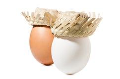 Bruine en witte eieren met strohoed die op witte achtergrond wordt geïsoleerd Stock Afbeeldingen