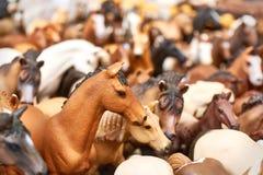 Bruine en witte stuk speelgoed paarden bij een vlooienmarkt stock foto