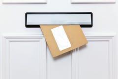 Bruine envelop in een voordeurbrievenbus Stock Afbeelding