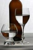Bruine fles en glazen Stock Afbeeldingen
