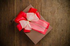 Bruine giftdoos met witte en rode boog stock afbeelding