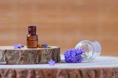 Bruine glasfles met lavendeletherische olie en verse bloemen op houten Stock Fotografie