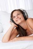 Bruine haar glimlachende vrouw met hoofdtelefoons Stock Afbeeldingen