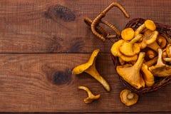 Bruine houten achtergrond met decoratieve mand met oranje paddestoelencantharellen Royalty-vrije Stock Foto's