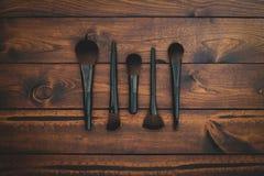 Bruine houten achtergrond met geassorteerde make-upborstels stock afbeeldingen