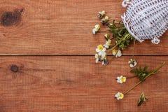 Bruine houten achtergrond met gele wilde viooltjes en witte kruik Royalty-vrije Stock Foto's