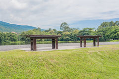 Bruine houten bank bij een groen meer Royalty-vrije Stock Foto's