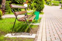 Bruine houten bank dichtbij de steeg in het park De zomer is buiten, glanst de zon stock foto