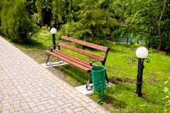 Bruine houten bank dichtbij de steeg in het park De zomer is buiten, glanst de zon stock afbeelding