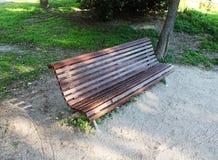 Bruine houten bank met zetels aan één kant in het park stock afbeelding