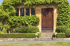 Bruine houten deuren aan traditioneel Engels gestenigd plattelandshuisje, tuin Royalty-vrije Stock Fotografie