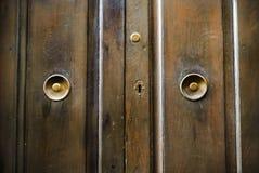 Bruine houten deuren met metaalhandvatten van een ongebruikelijke vorm Royalty-vrije Stock Afbeeldingen