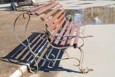 Bruine houten die bank in het stadspark, door zonlicht wordt verlicht royalty-vrije stock afbeeldingen