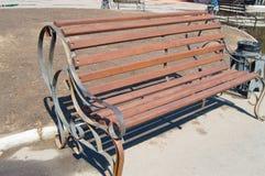 Bruine houten die bank in het stadspark, door zonlicht wordt verlicht royalty-vrije stock fotografie