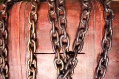 bruine, houten die kist, een spaarvarken, een borst met een slot van ijzer sterke kettingen wordt gesloten Stock Foto's