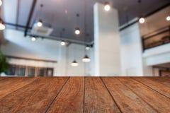 Bruine houten lijstbovenkant met de abstracte winkel van de onduidelijk beeldkoffie Stock Fotografie