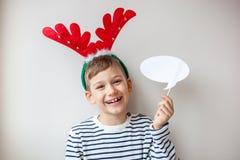 Bruine jonge jongen in een feestelijke stemming die en witte berichtbel glimlachen houden Stock Fotografie