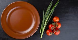 Bruine kleischotel en tomatoess op zwarte achtergrond Stock Fotografie