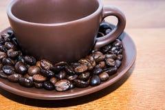 Bruine Koffiebonen en Kop Stock Afbeeldingen
