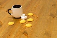 Bruine kop, kubussen van suiker en koekjes op houten lijst Royalty-vrije Stock Afbeeldingen