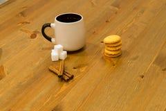 Bruine kop, kubussen van suiker en koekjes op houten lijst met kaneel Stock Foto