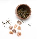 Bruine kristalsuiker en een theekop met groene thee stock afbeelding