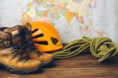 Bruine laarzen, een sportenkabel en een speciale helm een helm tegen de achtergrond van een geografische kaart Selectieve nadruk stock afbeeldingen