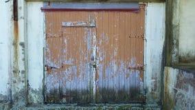 Bruine landbouwbedrijfdeuren met langzaam verdwenen verf en roest Stock Foto's