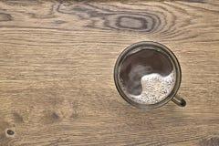 Bruine mok met hete koffie op houten achtergrond Royalty-vrije Stock Afbeeldingen