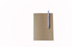 Bruine notitieboekje en pen stock afbeelding