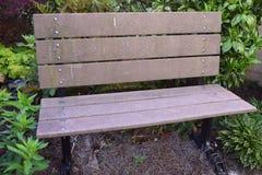 Bruine parkbank voor rust in tuin het plaatsen stock afbeelding