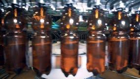 Bruine plastic die flessen met bier, dichte omhooggaand worden gevuld stock footage