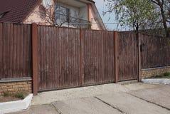 Bruine poort van houten planken en een deel van de omheining op een landelijke straat stock afbeelding