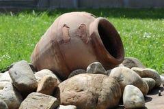 Bruine pot op rotsen in de tuin stock fotografie