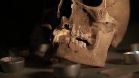 Bruine schedel in de cirkel van kaarsen, op een rokerige mistige achtergrond, Halloween-thema De vlam van kaarsen gaat uit stock video