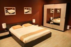 Bruine Slaapkamer Muur : Slaapkamer met bruin muren en kersenhardhout stock afbeelding