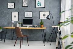 Bruine stoel bij bureau in grijs freelancer` s binnenland met lamp en stock afbeelding