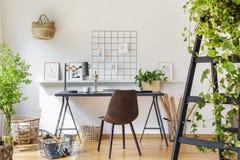 Bruine stoel bij bureau in wit het bureaubinnenland van het bohohuis met plan stock afbeeldingen